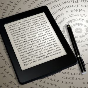 modern ebook reader on book on abstract font background